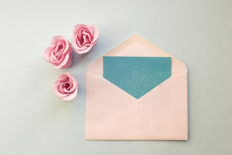 white envelope, blue blank card, three pink rose flowers on a blue background. Minimal Flat lay royalty free stock photography