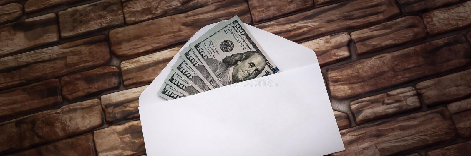White envelope with five hundred dollar bills on the background of a dark brick wall. stock photos