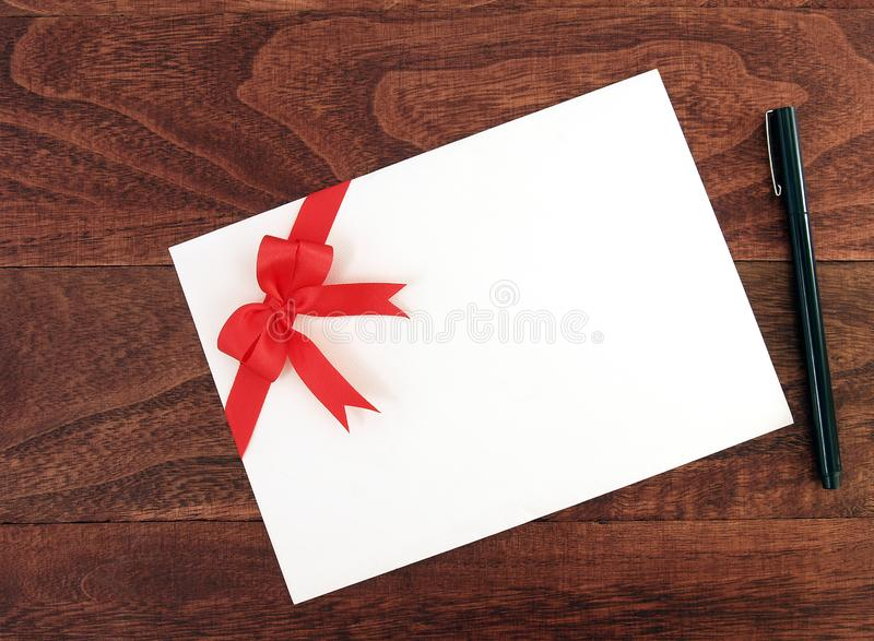 White envelope of invitation or greeting card with simple red ribbon double tied bow and black pen on dark brown wooden table top. Single white envelope of royalty free stock photography