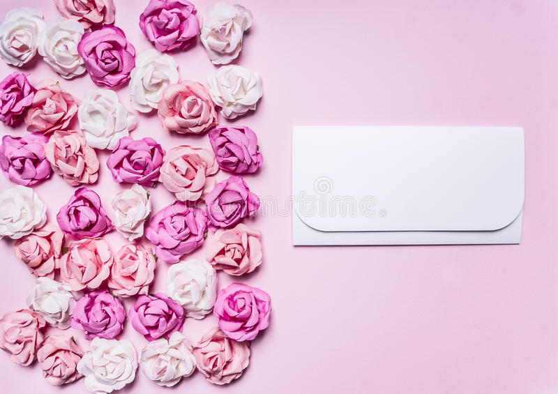 White envelope on a pink background colorful paper roses decorations Valentine's Day border ,place text top view clo. White envelope on a pink background with royalty free stock photography