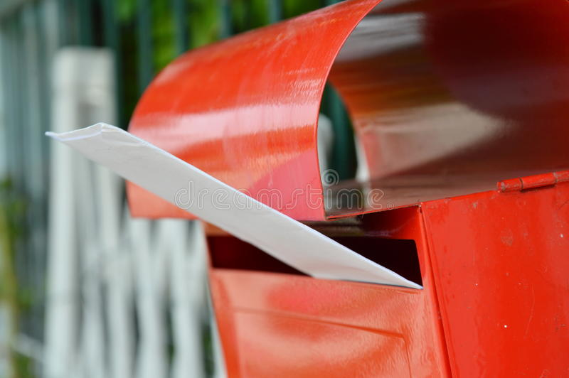 White envelope in red mail box on home fence stock photos