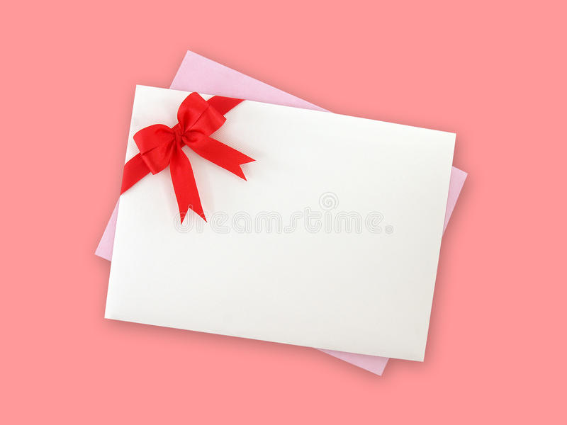White envelope with simple red ribbon double tied bow and light purple invitation or greeting card isolated on pink background. Flat lay close up top view with stock photography