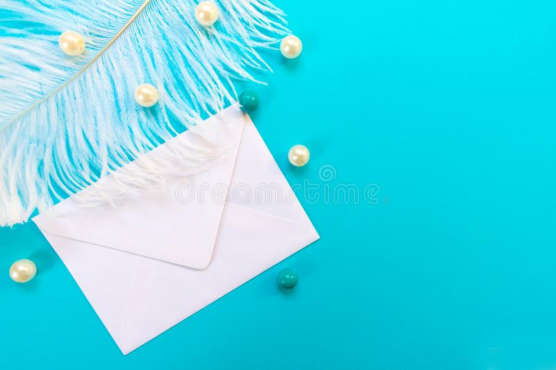 White envelope with white feather and beads isolated on blue background. Greeting card concept. stock image