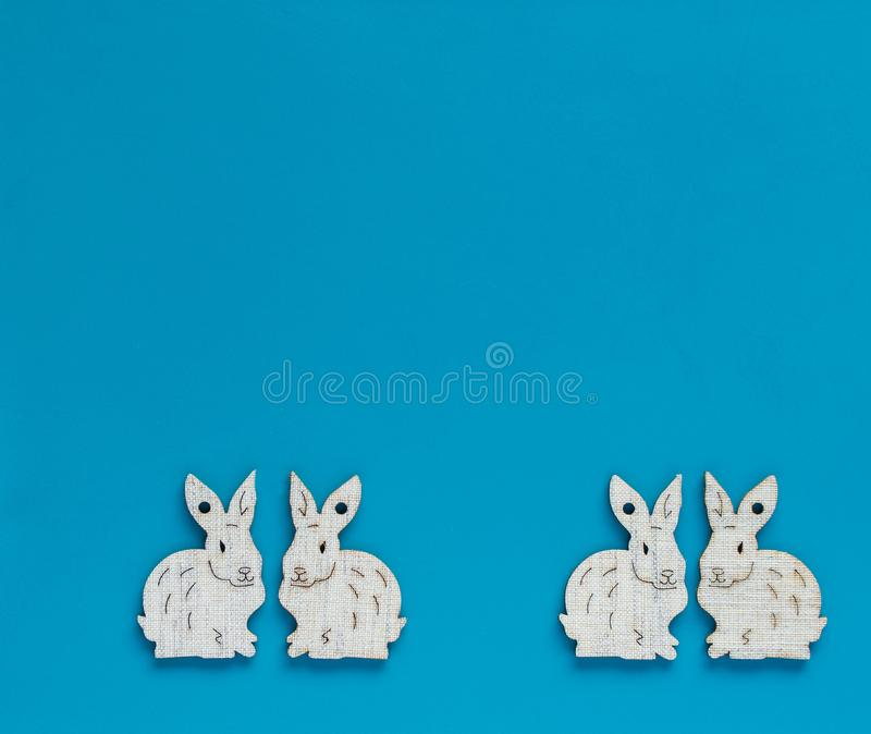White bunnies on blue background. White esater bunnies lined up at the bottom of blue copyspace, facing each other forming pairs - easter background stock images