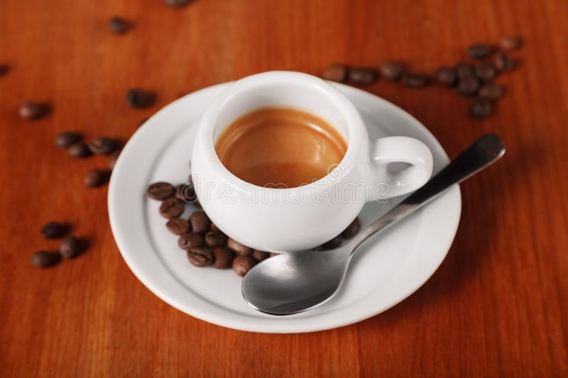 White espresso coffee Cup closeup, roasted coffee beans on wooden background. Concept of coffee break and serving coffee stock image