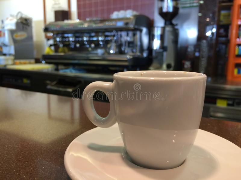 White Coffee Cup with Espresso Machine Background. White espresso coffee cup in the foreground with a blurred espresso machine in the background. Italian coffee stock images