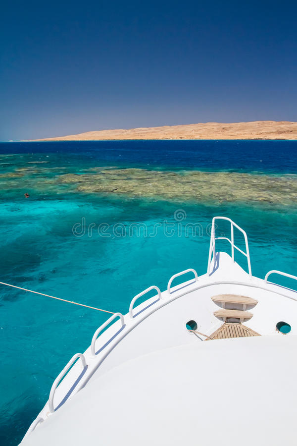 The white excursion yacht moored beside the island Giftun. Snorkeling point tourists and motor yachts on Red Sea. Popular and famous tourists destination in royalty free stock image