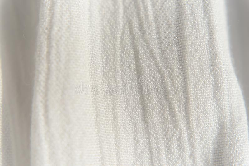 White fabric background texture close up. White thin fabric, with vertical folds royalty free stock photo