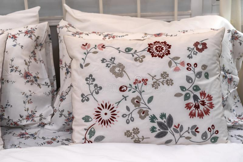 White fabric pillows with beautiful embroidered flower patterns on the bed interior. Modern white fabric pillows with beautiful embroidered flower patterns on stock image