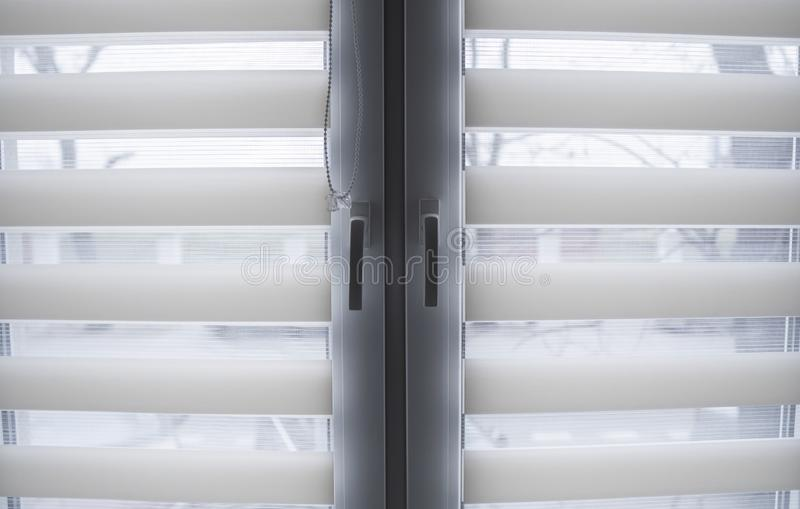 White fabric roller blinds on the white plastic window in the living room. Roll curtains indoor. White fabric roller blinds on the white plastic window in the stock photos