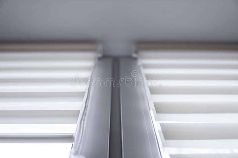 White fabric roller blinds on the white plastic window in the living room. Roll curtains indoor. White fabric roller blinds on the white plastic window in the stock photo