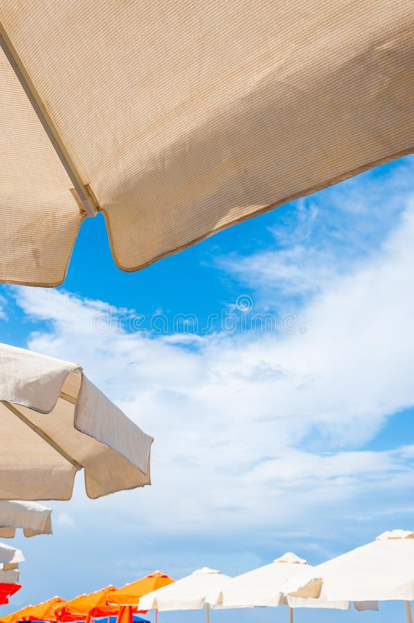 White fabric sun umbrellas parasol close-up from below with blue sky on the background royalty free stock image