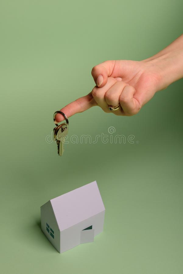 White family paper house. House keys in hand on mint background paper. Minimalistic and simple concept, style. Copy space. Vertical orientation. Family moving stock image