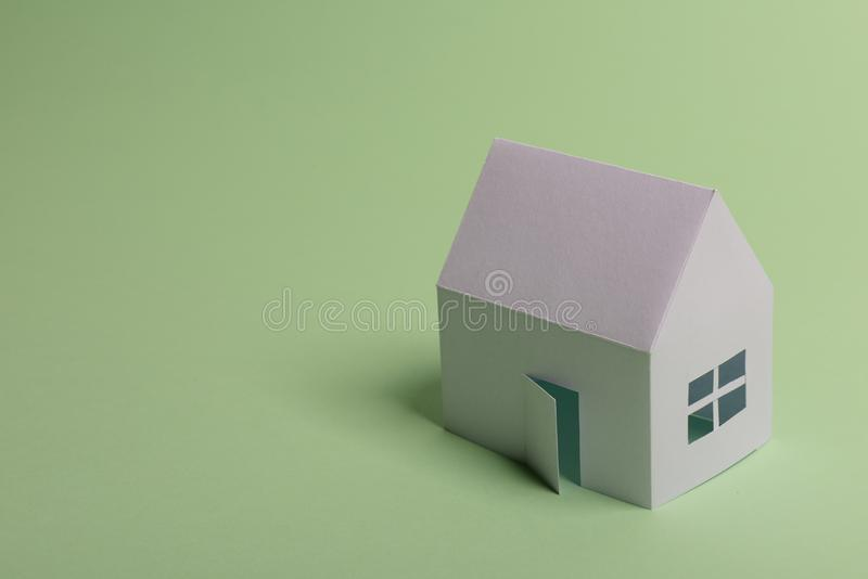 White family paper house in man hand on mint background paper. Minimalistic and simple concept, style. Copy space. Horizontal. Orientation, estate, home royalty free stock photos