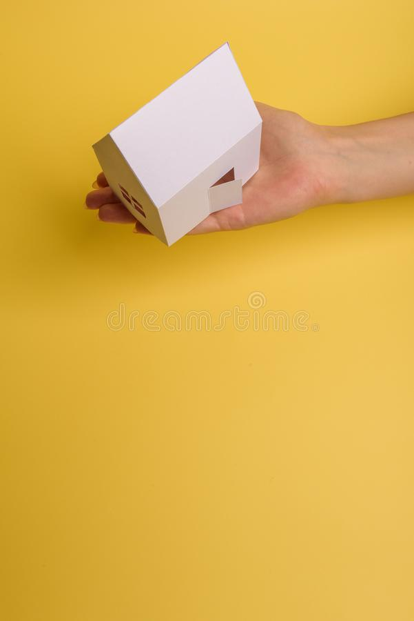 White family paper house in man hand on yellow background paper. Minimalistic style. Copy space. View from above. Horizontal. Orientation, estate, home royalty free stock images