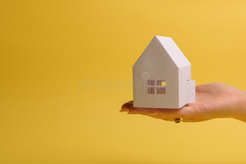 White family paper house in man hand on yellow background paper. Minimalistic style. Copy space. View from above. Horizontal. Orientation, estate, home stock photography