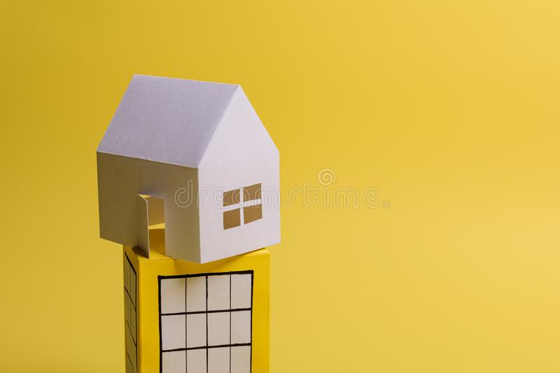 White family paper house over block of flats on yellow background paper. Minimalistic and simple concept, style. Copy space. Vertical orientation, estate, home royalty free stock photos