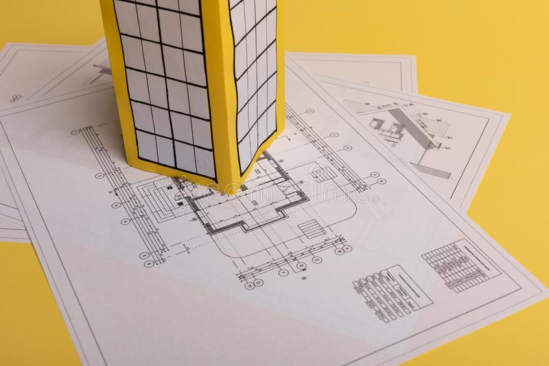 White family paper house, house projects plan and blueprints on yellow background paper. Minimalistic and simple concept, style. Vertical orientation, estate royalty free stock images