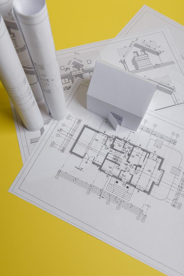 White family paper house, house projects plan and blueprints on yellow background paper. Minimalistic and simple concept, style. Vertical orientation, estate stock image