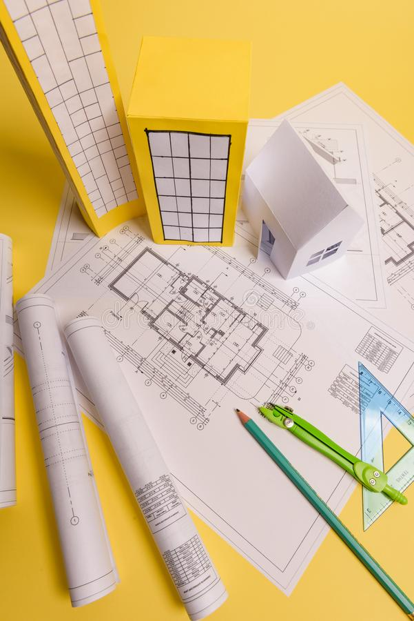 White family paper house, house projects plan and blueprints on yellow background paper. Minimalistic and simple concept, style. Vertical orientation, estate royalty free stock photo