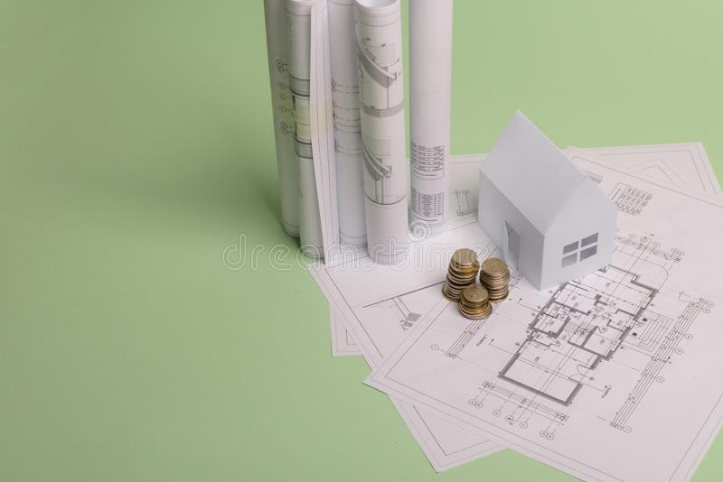 White family paper house , stack of money coins, house projects plan and blueprints on mint background paper. Minimalistic and. Simple concept, style royalty free stock photo