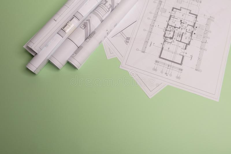 White family paper house , stack of money coins, house projects plan and blueprints on mint background paper. Minimalistic and. Simple concept, style stock photo