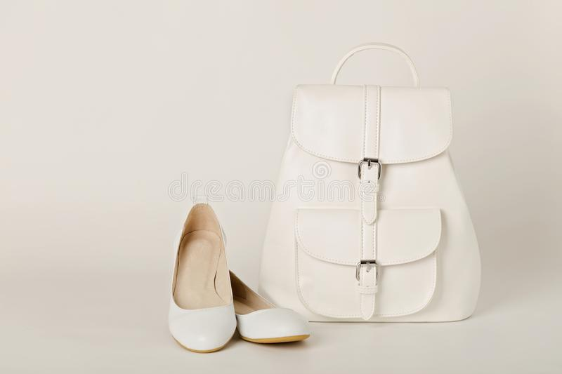 White female backpack and shoes on a white background. royalty free stock photos