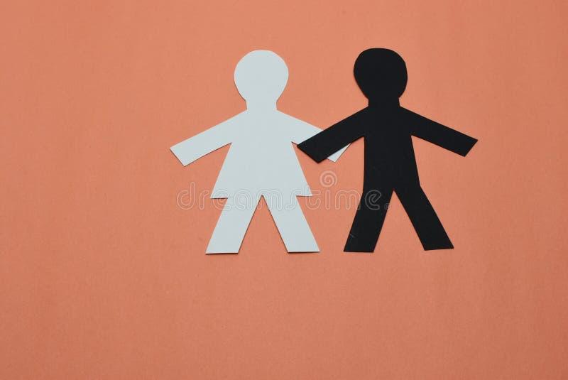 White female, black male silhouettes on orange background royalty free stock photo