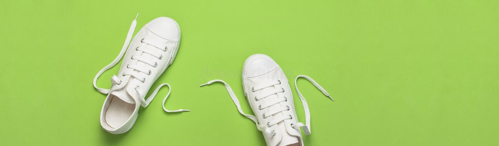 White female fashion sneakers on green background. Flat lay top view copy space. Women`s shoes. Stylish white sneakers. Fashion. Blog or magazine concept stock photos