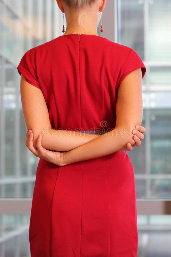 White female in red dress stretching arms on her back stock photo