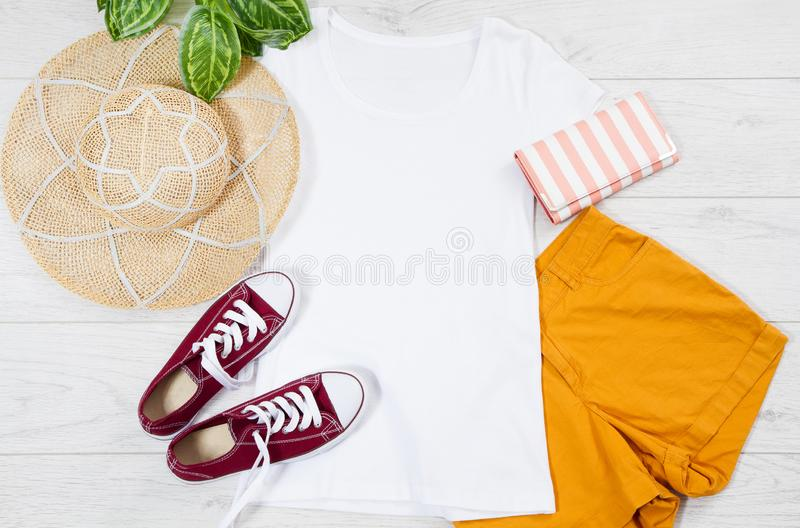 White female t shirt mock up flat lay on wooden background. Top view and copy space. Mockup t-shirt and summertime. Template blank royalty free stock photo