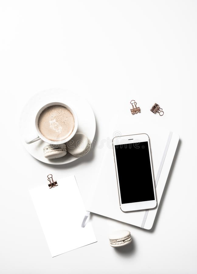 White feminine flat lay with beige macaroons, coffee and smartph stock photos