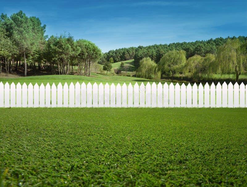 White fences on green grass stock photos