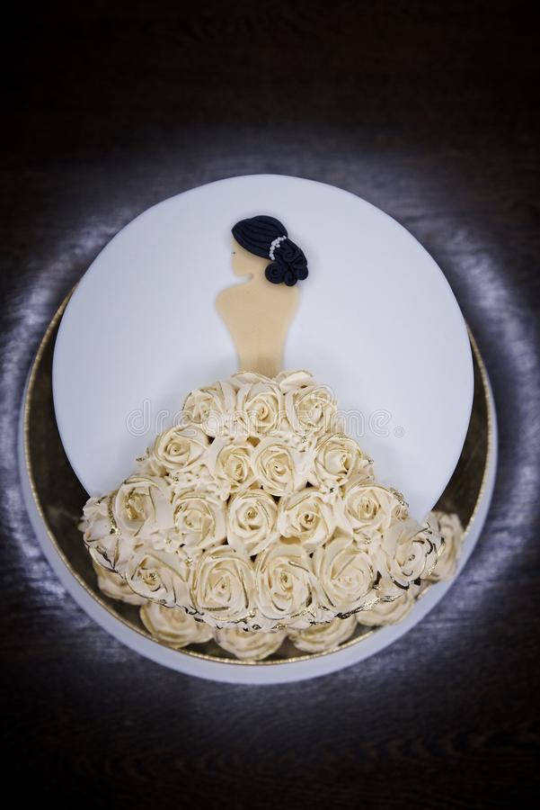 A white festive cake is adorned with a figure of a girl. In a dress of roses stock image
