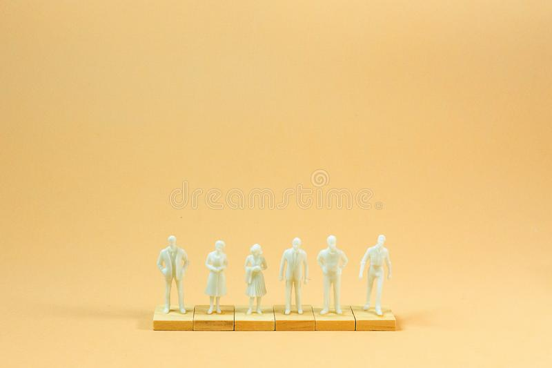 White  figure miniature on orange pastel for business content stock photography