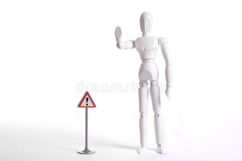 White figure with sign Attention. White figure with a symbolic stop gesture and danger symbol poles royalty free stock photo