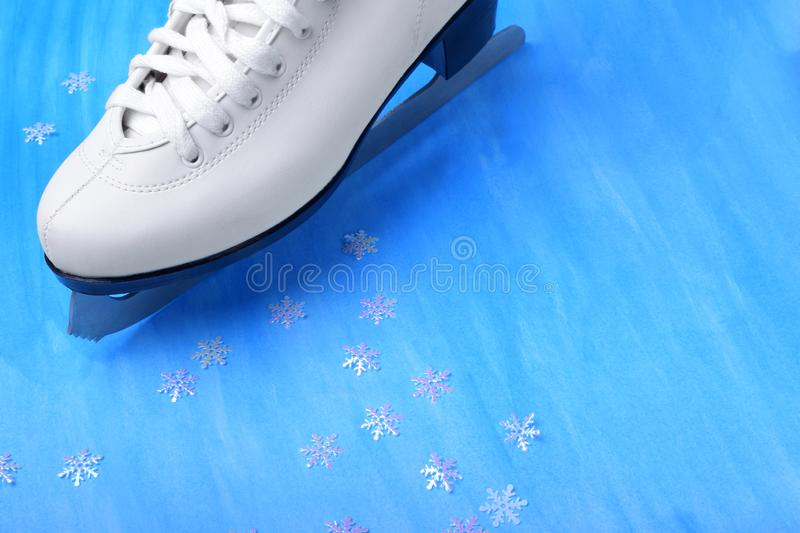 White figure skate against the blue background. Copy space royalty free stock photography