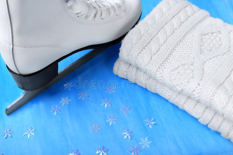 White figure skate and knitted scarf. Against the blue background royalty free stock photos