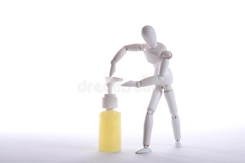 White figure with soap dispenser. White figure who wants to let soap out of a soap dispenser on her hand stock photos