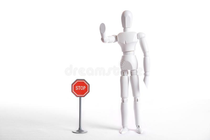 White figure with stop sign. White figure with a symbolic stop gesture and danger symbol poles royalty free stock photos