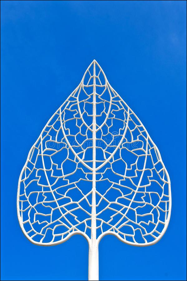 White filigree leaf. A cast iron white filigree leaf isolated against a blue sky background stock photos