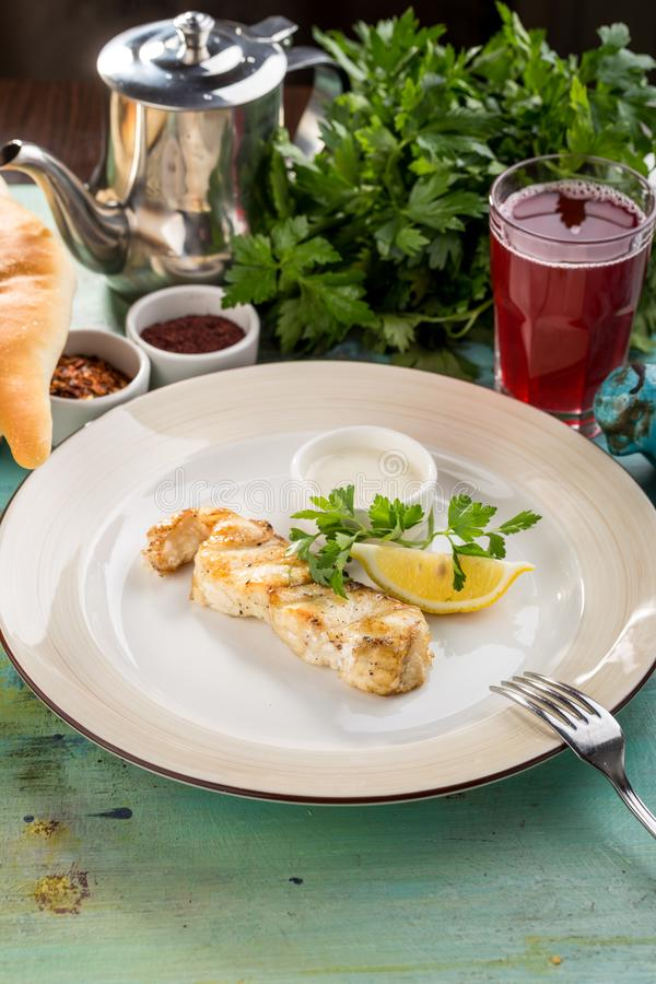 White fish fillet baked with lemon slice and white sauce on blue wooden table stock photo