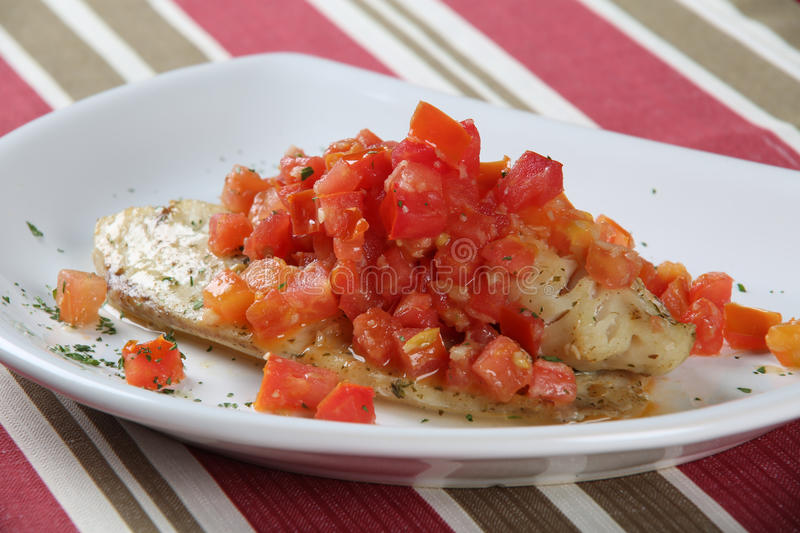 White fish fillets in rich tomato sauce royalty free stock image
