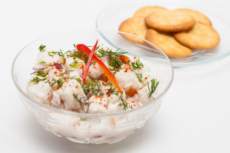 White fish Peruvian ceviche served in a transparent bowl with crackers stock photos