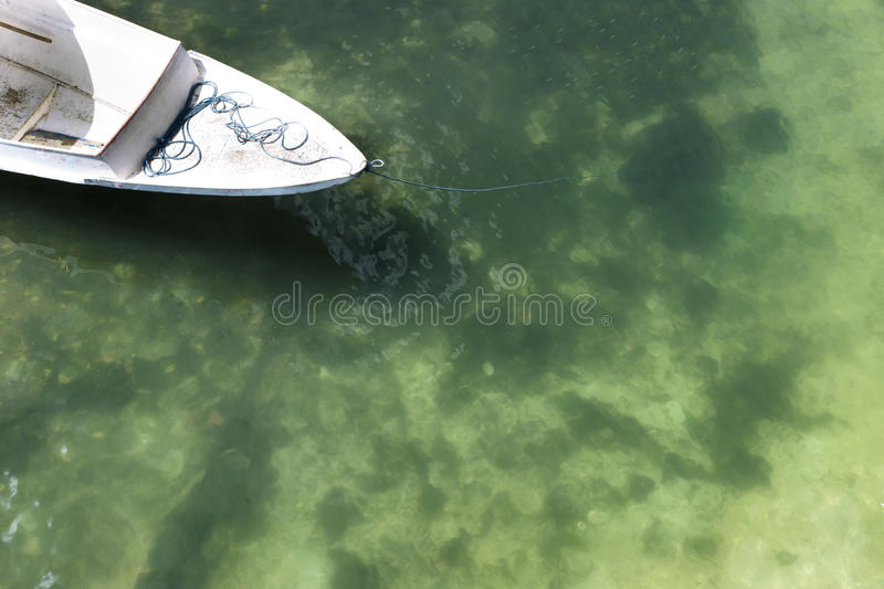 White fisherboat with green yellow water, Nusa Lembogan, Bali, Indonesia. White fisherboat on the shore with green yellow water, Nusa Lembogan, Bali, Indonesia royalty free stock photos