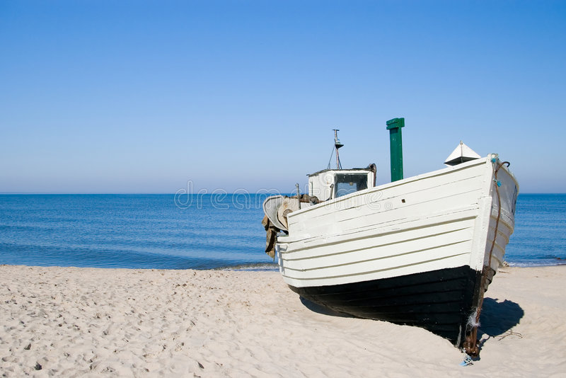 White fishing boat. A white fishing boat standing on the sand of a beach. Clear sky and horizon, nobody in the photo. The Baltic Sea royalty free stock photography