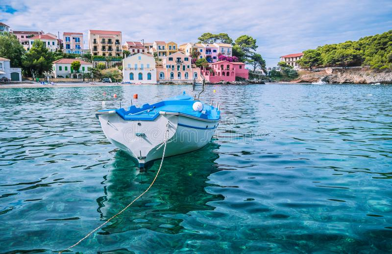 White fishing boat in the blue rippled sea water bay in Assos village, Kefalonia island, Greece stock images