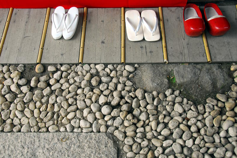 White flip-flops and red clogs. On wooden floor in a Shinto shrine stock image