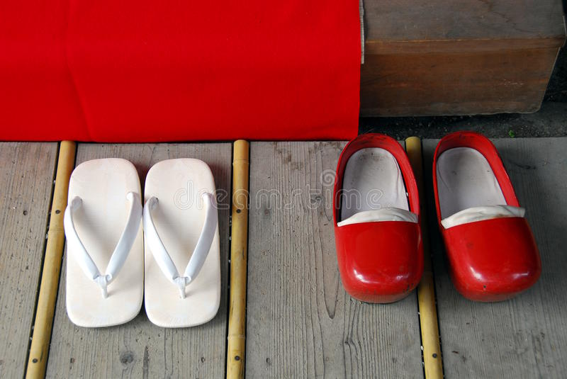 White flip-flops and red clogs. On wooden floor in a Shinto shrine stock images