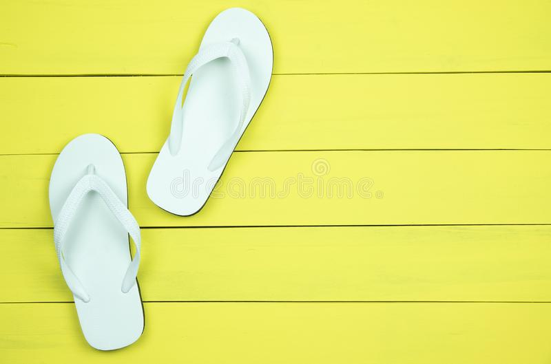 White flip flops on yellow wood background. royalty free stock image